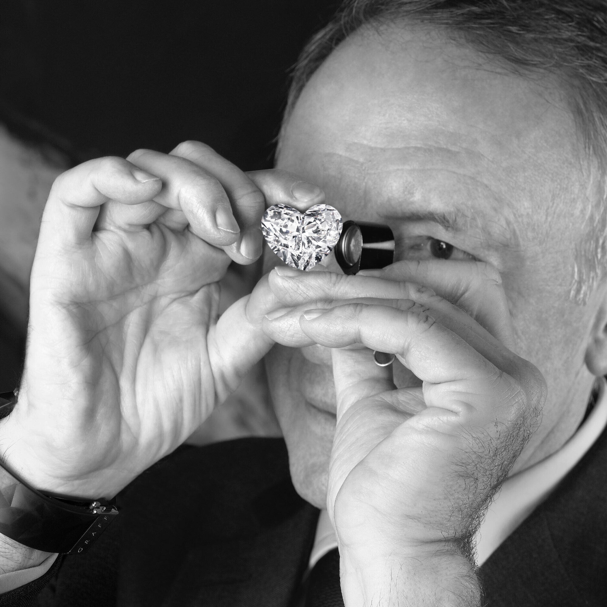 Mr Laurence Graff looking into a heart shape diamond through a loupe