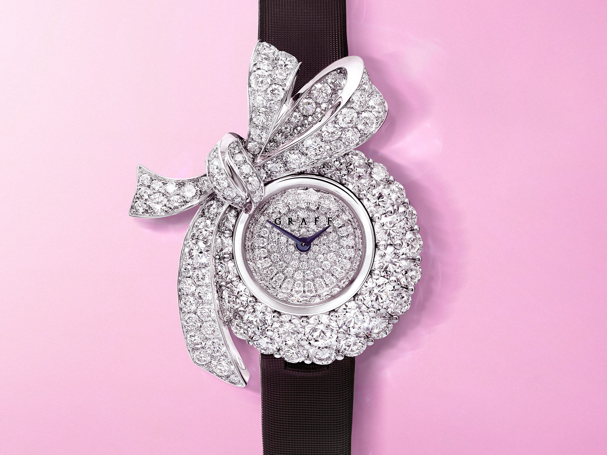 A Graff Tilda's Bow diamond watch with pear shape drop on a pink background
