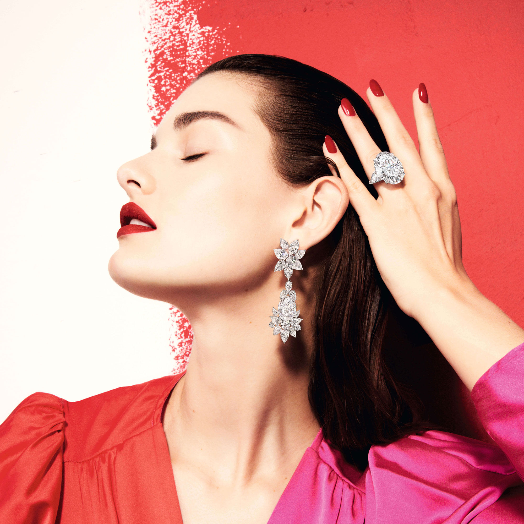 close up of a lady standing in front of a wall with red paint wearing Graff diamond earrings and ring
