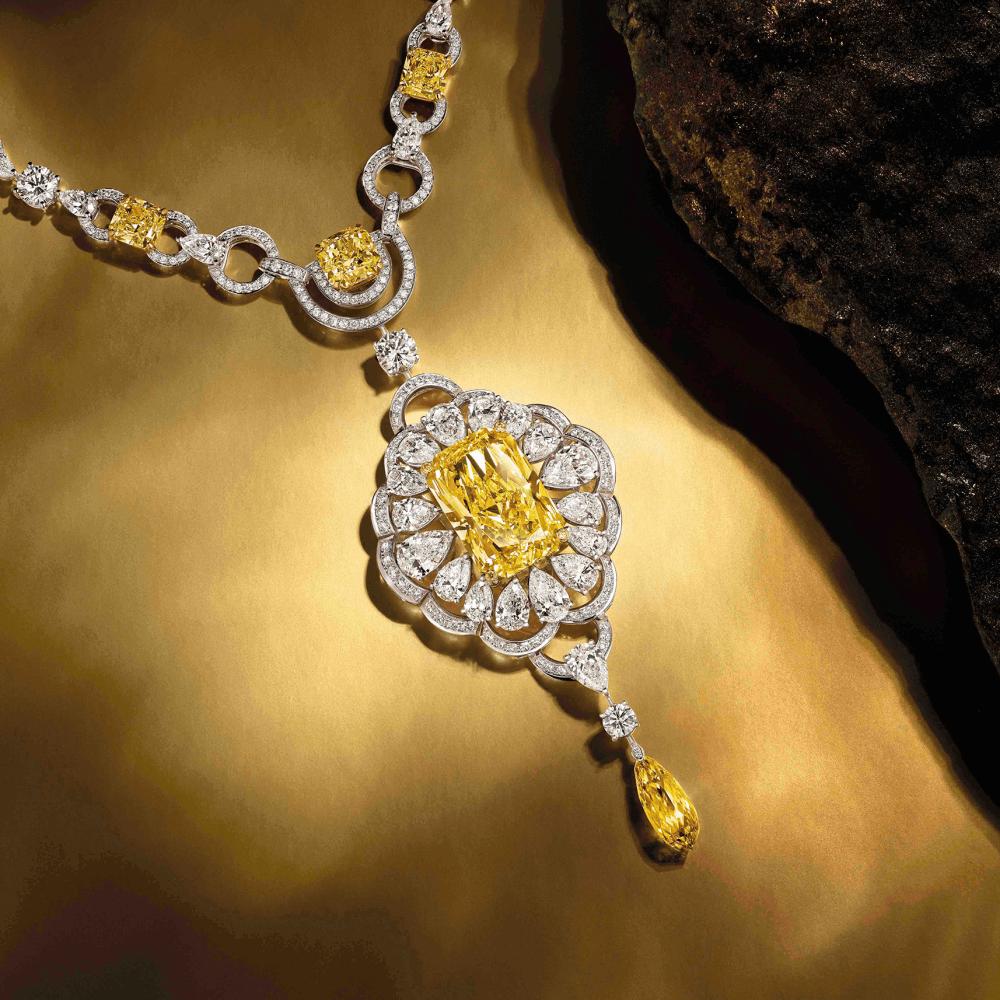 A Graff Yellow and White Diamond Necklace next to a stone