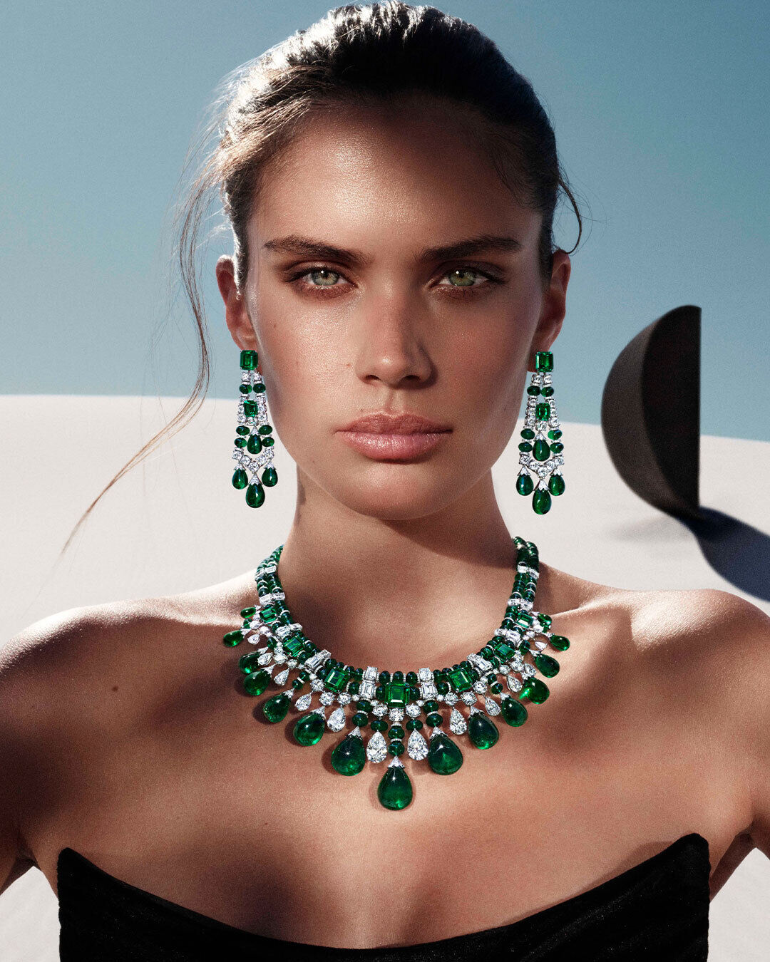 Sara Sampaio wears the Graff Tribal collection emerald and diamond high jewellery earrings and necklace, in a desert in front of the black sculpture
