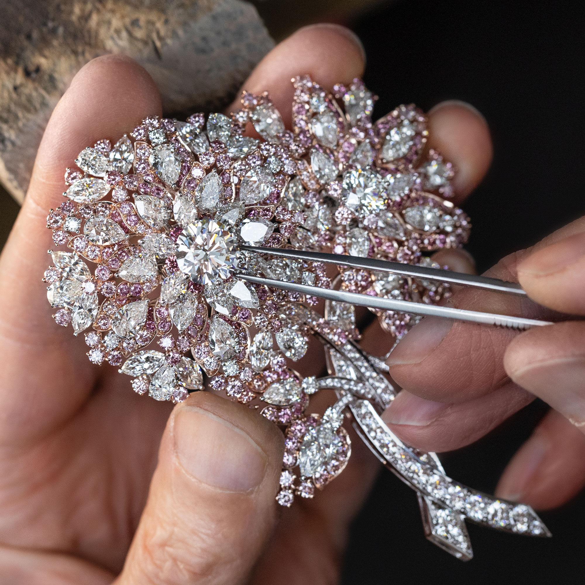 Close up of a Graff craftsman setting a pink and white diamond high jewellery brooch