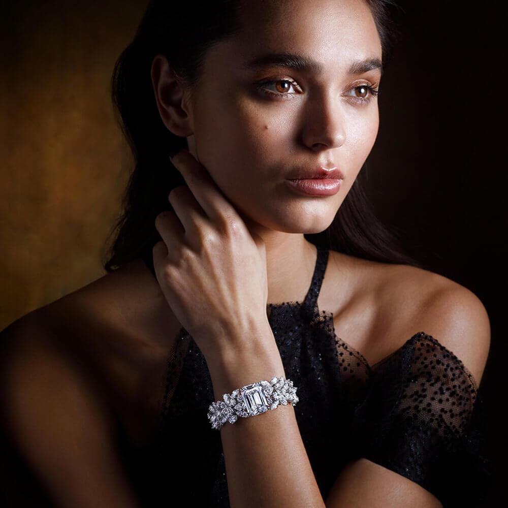 A lady wearing a Graff diamond bracelet featuring a 33.40 carat emerald cut diamond