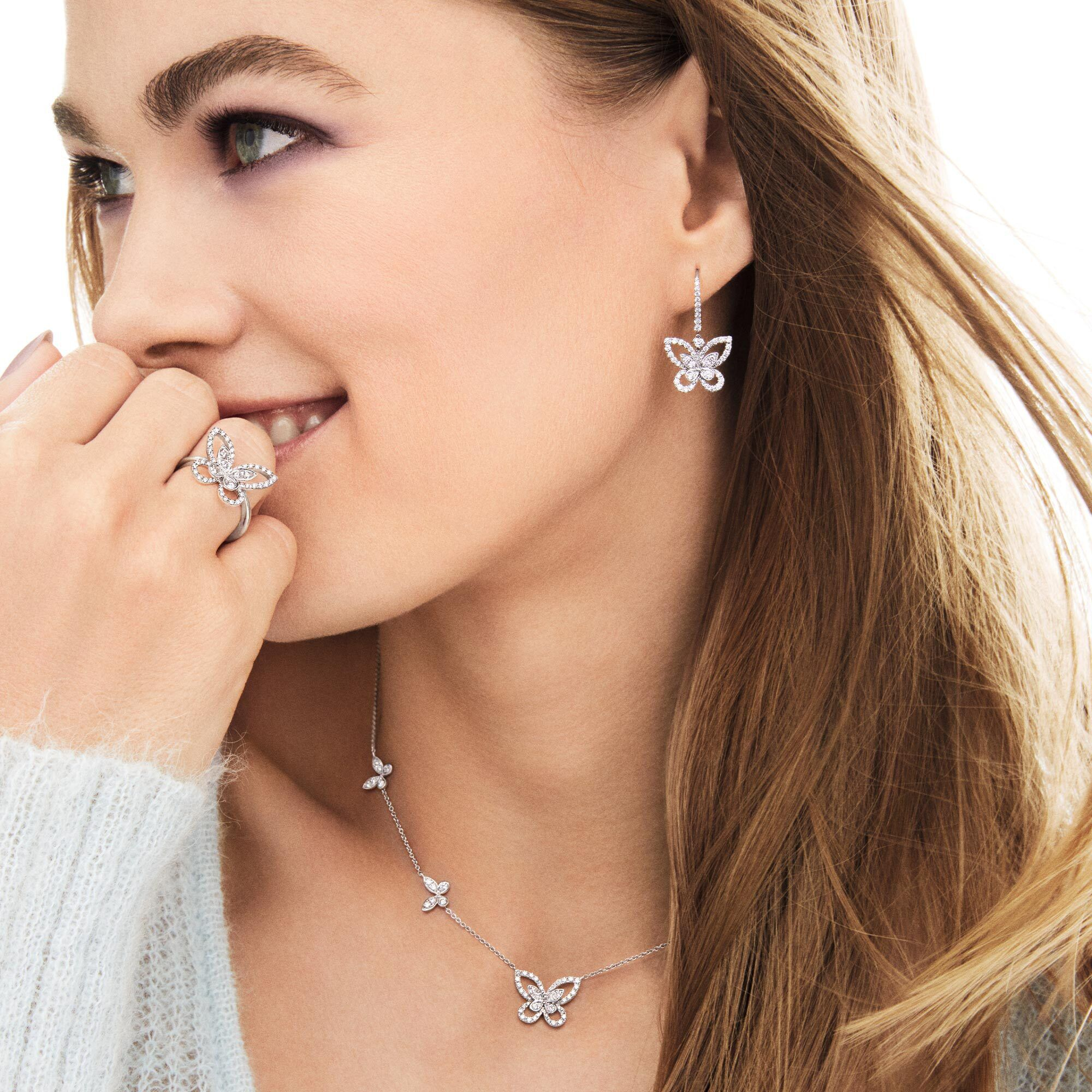 Close up of a model wearing the Graff Butterfly Silhouette jewellery collection diamond earrings, pendant and ring