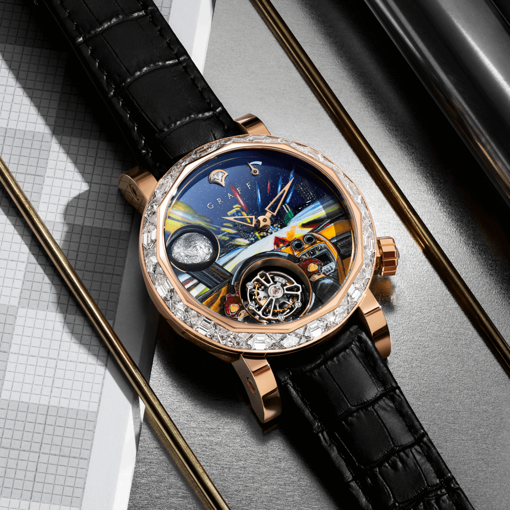 A Graff Men's GyroGraff Futuristic Drive watch with rose gold diamond bezel on a desk with stationeries