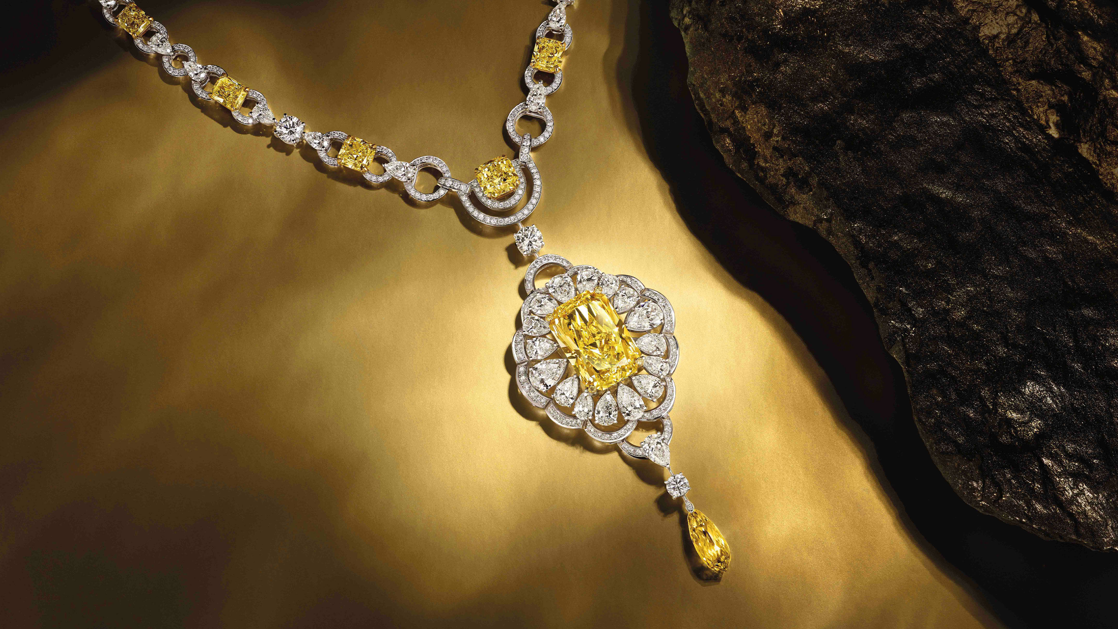 A Graff yellow and white diamond high jewellery necklace next to a rock