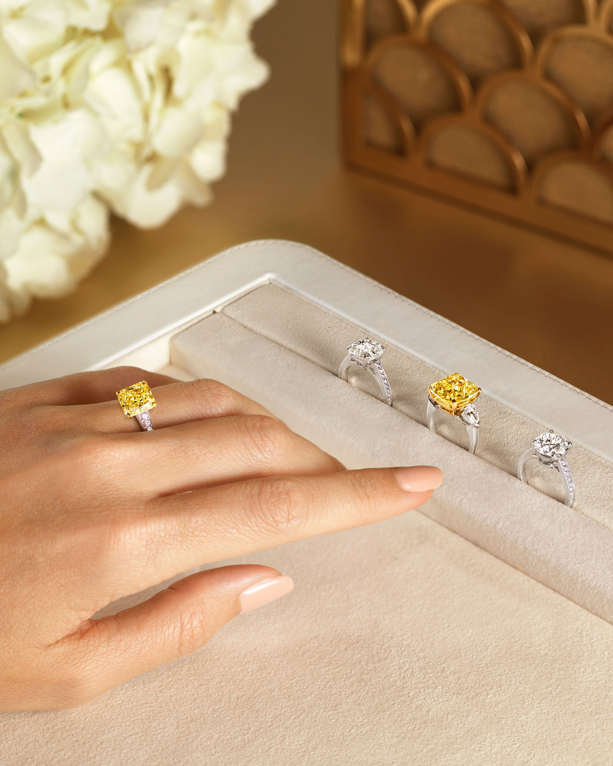 Close up of a model wearing a Graff yellow diamond ring with three diamond rings on a tray