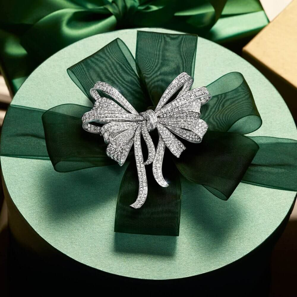A Graff Diamond Bow Brooch on a holiday season christmas green gift box placed on a piano next to other gift boxes