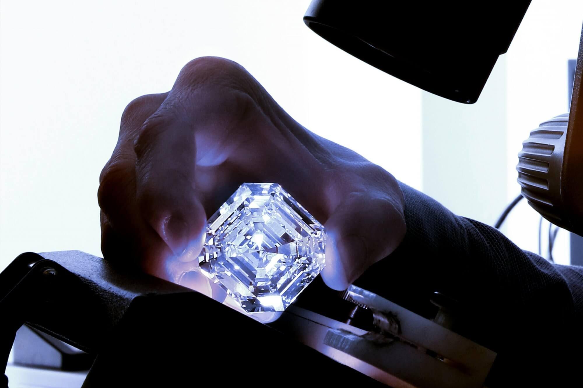 A Graff team member examining the Graff Lesedi La Rona Square Emerald Cut Diamond