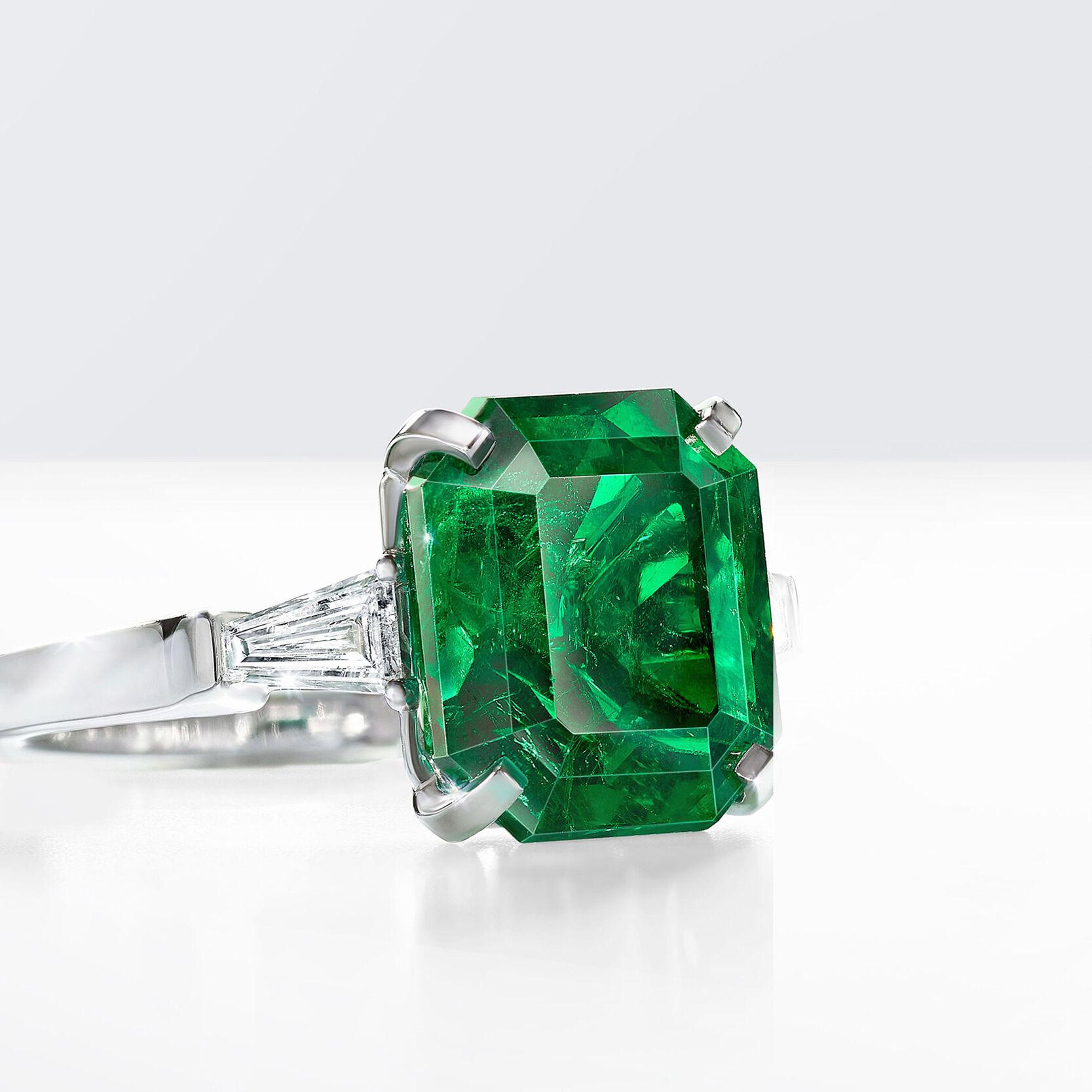 An emerald cut emerald ring with baguette cut side diamonds by Graff
