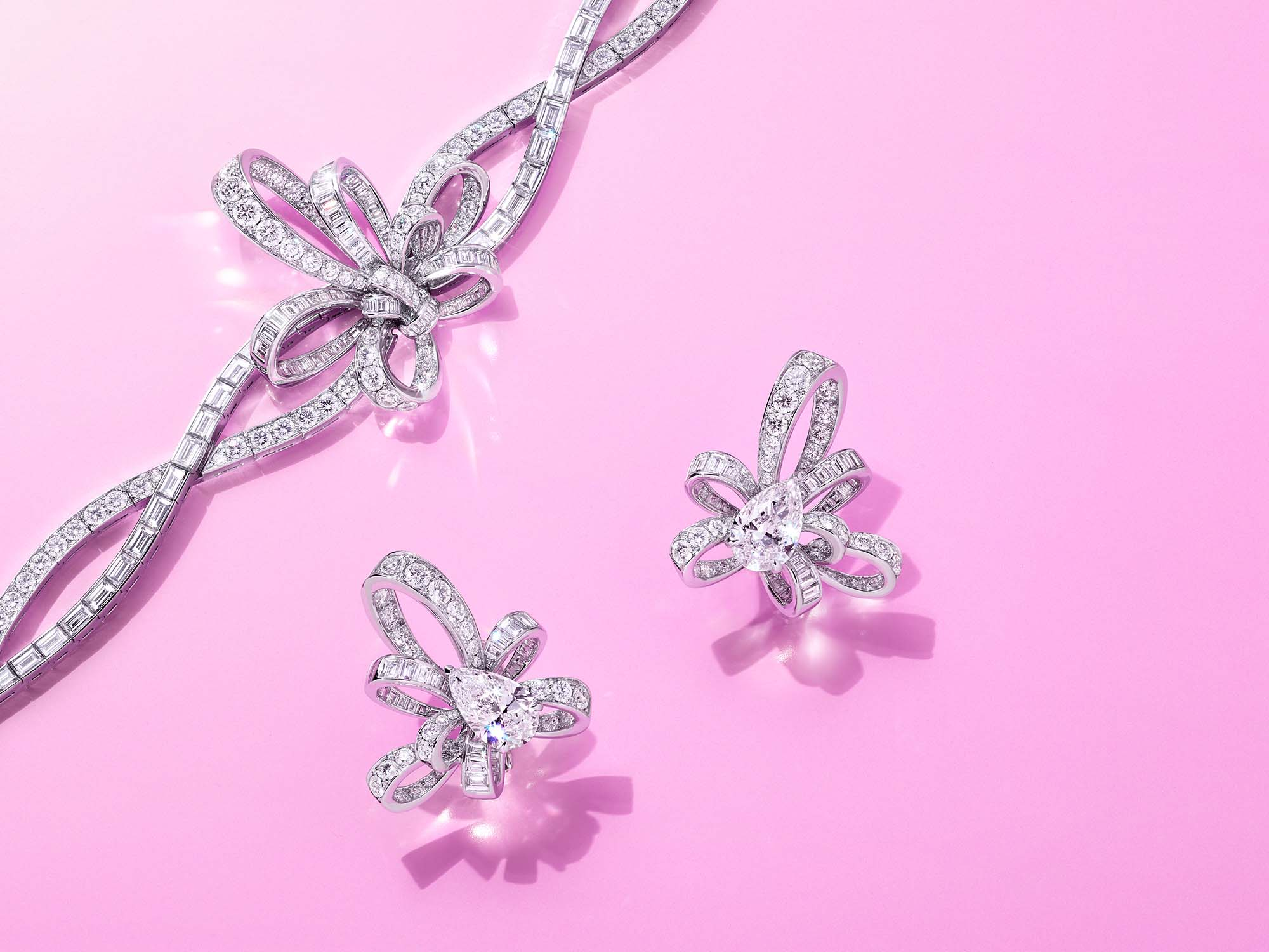 Graff Tilda's Bow jewellery collection diamond earrings and bracelet on a pink background